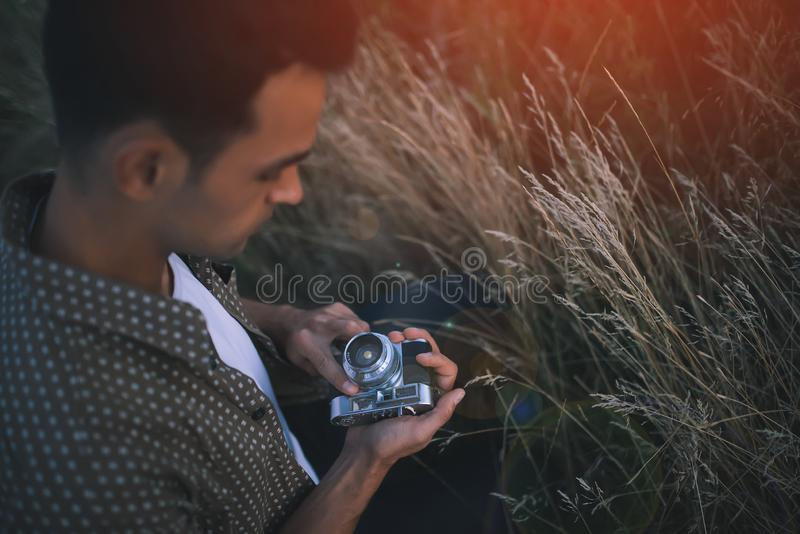 Взгляд сверху прелестного портрета конца-вверх молодого человека с винтажной камерой на поле, траве, природе, предпосылке Путешес стоковые фотографии rf