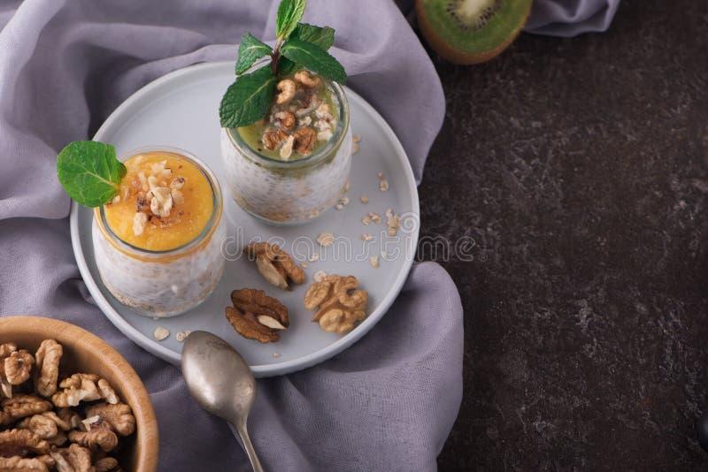 Взгляд сверху домодельного пудинга семян Chia и молока миндалины с хлопьями и пюрем кивиа и манго с грецкими орехами и мятой vega стоковая фотография rf