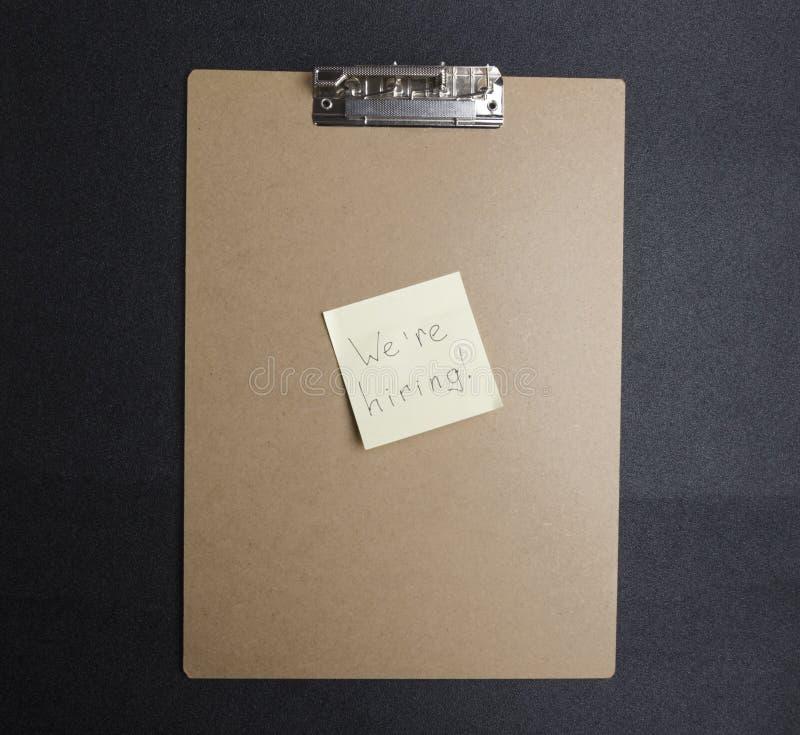 """Взгляд сверху доски сзажимом для бумаги и желтый стикер с рукой слова пишущ """"мы нанимаем """" Концепция искать работников стоковое фото"""