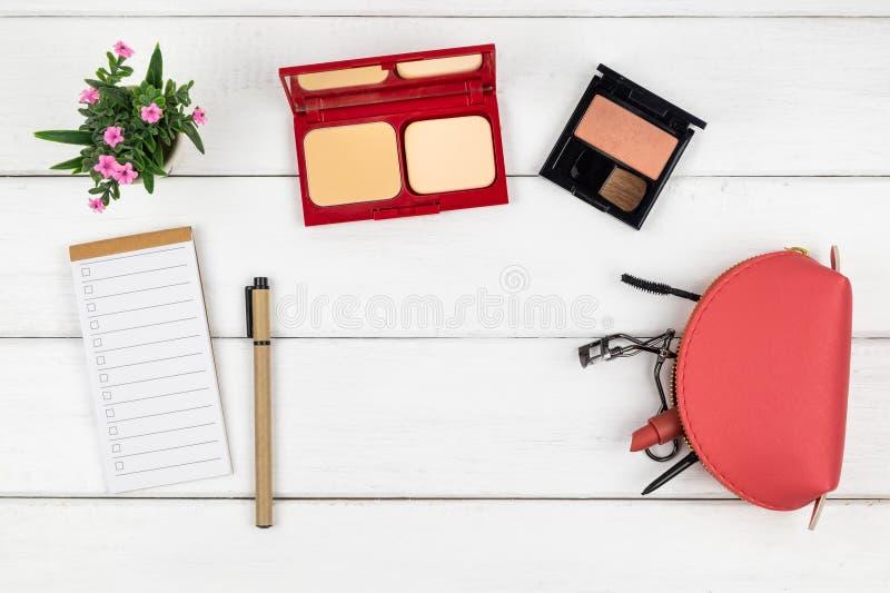 Взгляд сверху тетради и ручки косметик на деревянной предпосылке стоковые фото