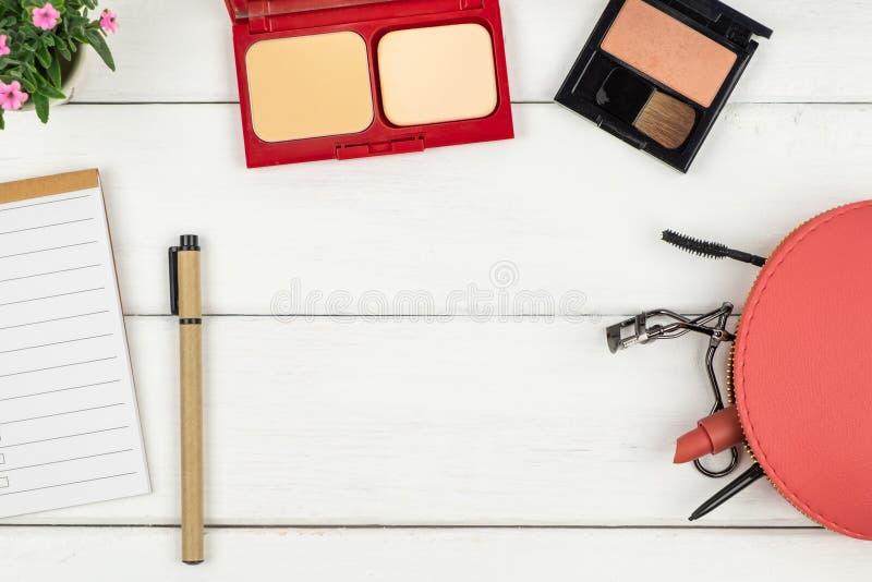 Взгляд сверху тетради и ручки косметик на деревянной предпосылке стоковые фотографии rf