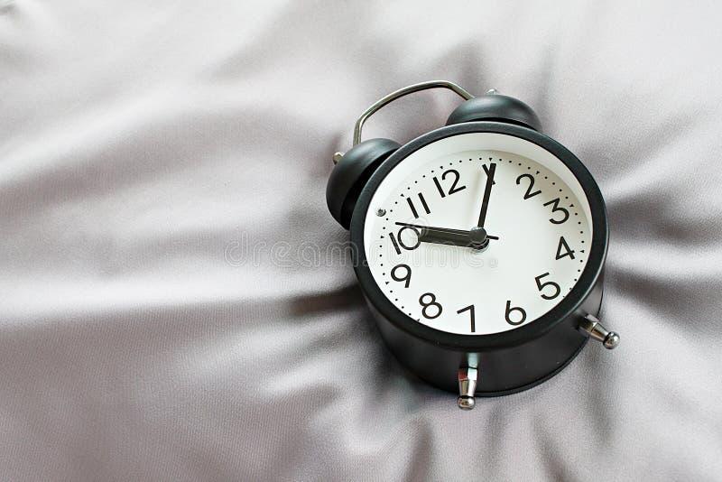 Взгляд сверху черного ретро будильника на кровати в утре, подготавливает для добавления или глумится вверх стоковое изображение