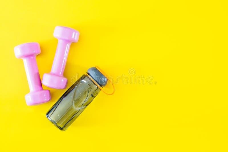 Взгляд сверху розовых гантелей и бутылка воды на желтой предпосылке Фитнес и здоровая концепция предпосылки образа жизни стоковые изображения