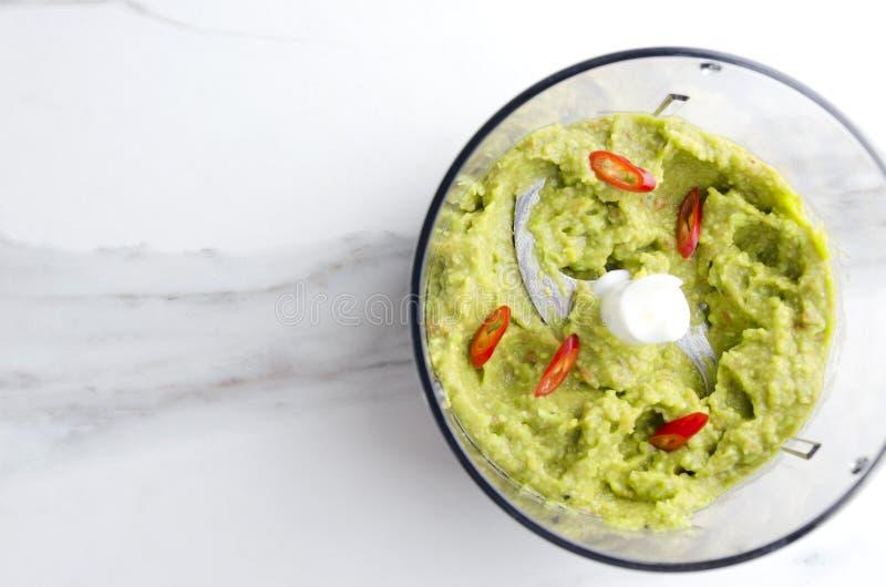 Взгляд сверху blender и смешанного гуакамоле с перцем чилей Концепция погружения подготовки основанного на авокадо в кухне стоковые изображения