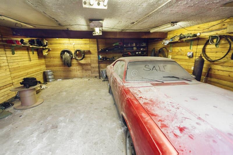 Взгляд старого автомобиля в гараже с экраном ветра пылевоздушного клобука пакостным с ПРОДАЖЕЙ названия пальцем и сломленным счищ стоковое изображение