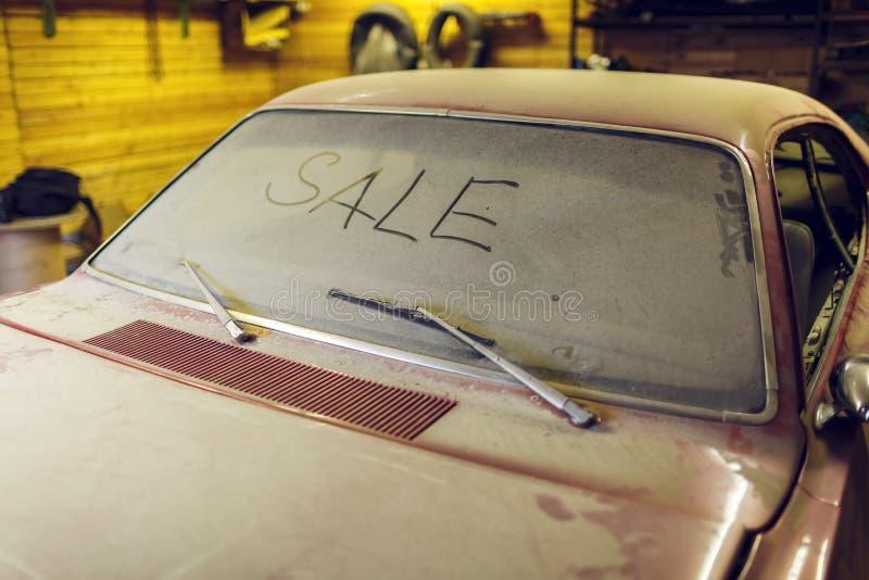 Взгляд старого автомобиля в гараже с экраном ветра пылевоздушного клобука пакостным с ПРОДАЖЕЙ названия пальцем и сломленным счищ стоковые фото