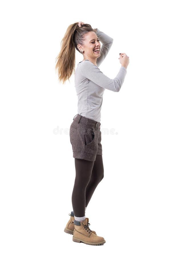 Взгляд со стороны беспристрастной стильной молодой девушки хипстера держа волосы в кабеле и смеясь с закрытыми глазами стоковое фото