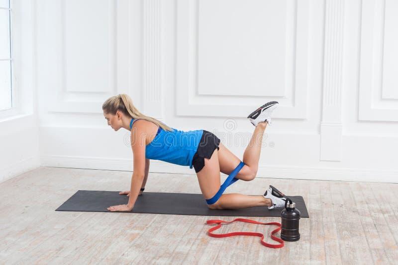 Взгляд со стороны сильной и подходящей атлетической молодой красивой кавказской женщины в sportwear с диапазонами тренируя ноги и стоковые изображения rf