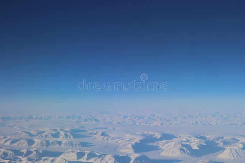 Взгляд от самолета к снежной Гренландии Ландшафт снежных гор Гренландии стоковая фотография rf