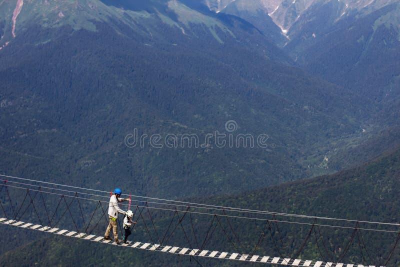 Взрослый и движение ребенка над висеть моста высокий в горах стоковая фотография