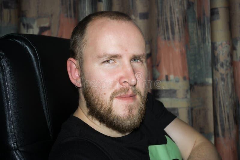 Взрослый человек удобно усажен в поддерживаемый высоко стул компьютера, слушает внимательно стоковые фотографии rf