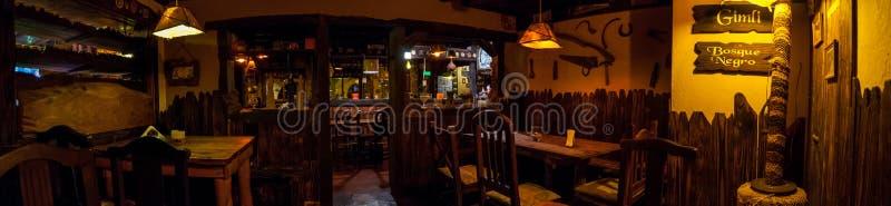 ВИЛЛА GESELL, ARGENTINA-MARCH 21,2018: Панорамный интерьера ирландского паба Перевод темного леса на испанском стоковая фотография