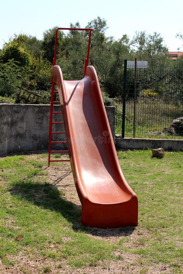Винтажное ретро старое красное пластиковое скольжение спортивной площадки с лестницами металла окруженными с травой и каменная ст стоковое изображение rf