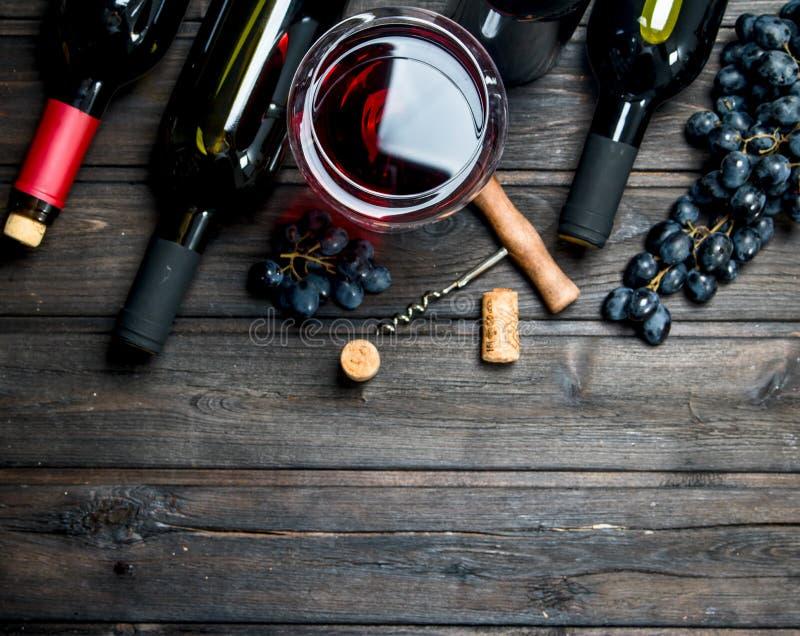 вино предпосылки стеклянное красное Красное вино с виноградинами и штопором стоковое фото