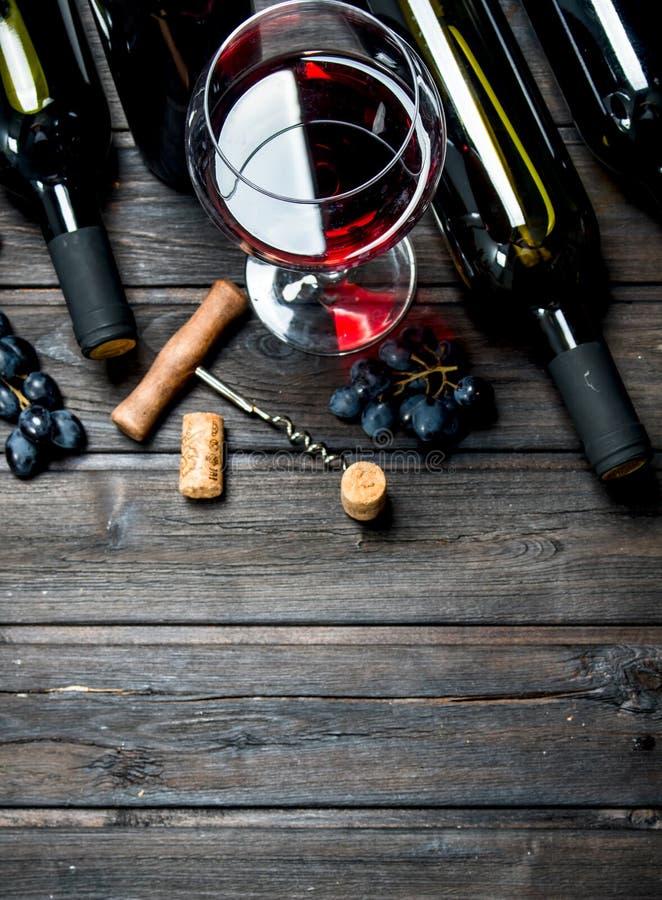 вино предпосылки стеклянное красное Красное вино с виноградинами и штопором стоковое изображение