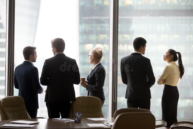 Вид сзади международных исполнительных властей объединяется в команду говорить около окна офиса стоковые изображения