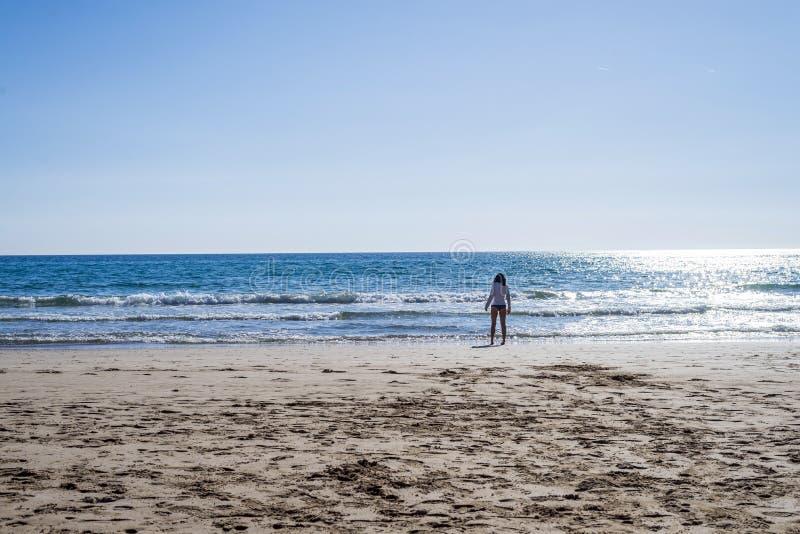 Вид сзади сиротливого положения женщины на трусах seashore нося в солнечном дне стоковые фото