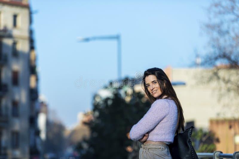 Вид спереди усмехаясь красивой руки молодой женщины на кармане, касающся волосам и стоящ в улице пока смотрящ прочь в солнечном стоковое фото