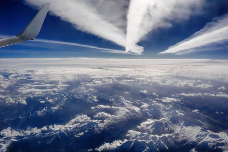 Вид с воздуха снежных гор, облаков и плоских следов, напротив солнечного света стоковое изображение rf