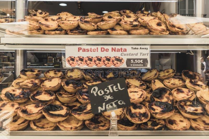 Витрина пекарни в городе Лиссабона с много типичных тортов сливк от Португалии стоковые фото
