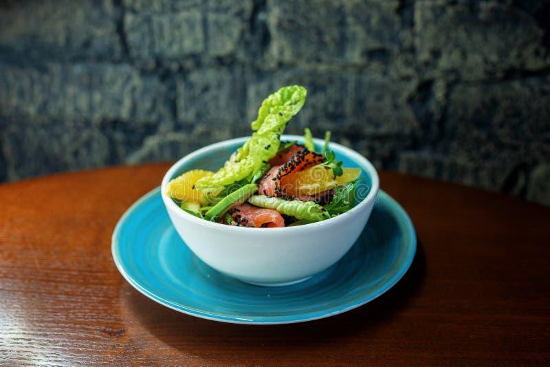Вкусный салат с филе семг со свежими овощами и кусок апельсина на таблице в ресторане вкусный обед стоковые фото