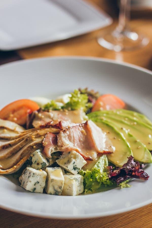 Вкусный свежий салат с различными ингредиентами как салат, томатами, мясом, сыром в ресторане на белой плите стоковая фотография rf