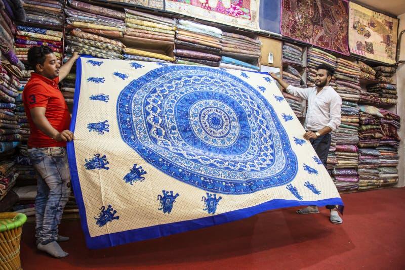 Владелец фабрики ткани с его ассистентом показывая handmade напечатанные листы мандалы хлопка стоковое изображение rf