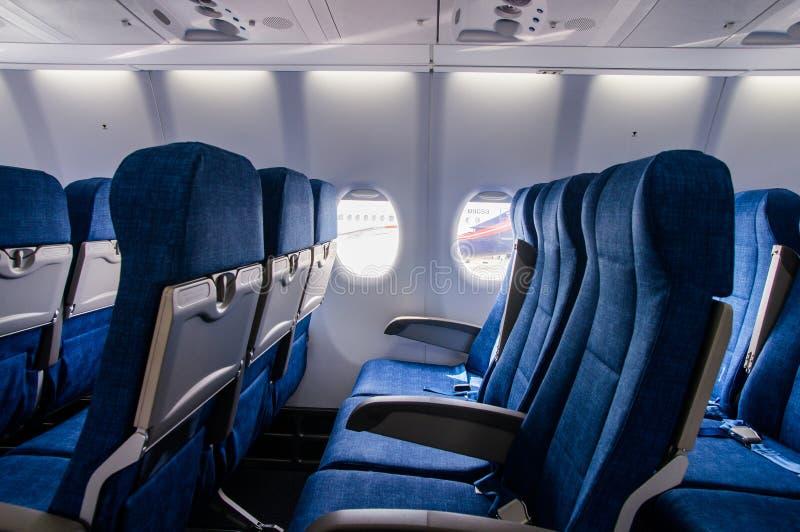 Внутренний взгляд внутренности мест тренера экономики самолета пассажира стоковое фото