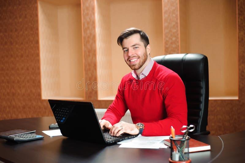 Вскользь бизнесмен работая с компьютером в офисе, смотрящ камеру, усмехаясь стоковое изображение rf