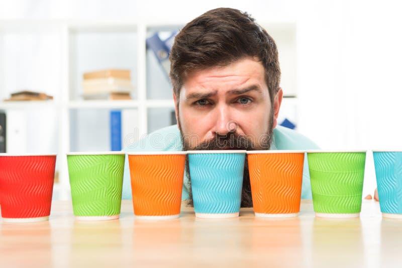 Выберите от альтернатив Человек бородатое выбирая одно бумажных стаканчиков серии красочных Альтернативная концепция Выбор одно р стоковые фото