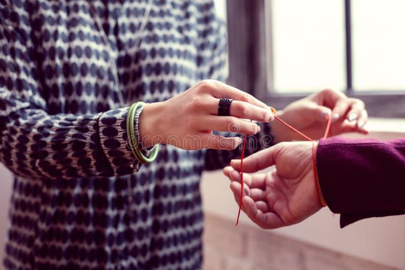 Выборочный фокус красного браслета на мужской руке стоковые фото