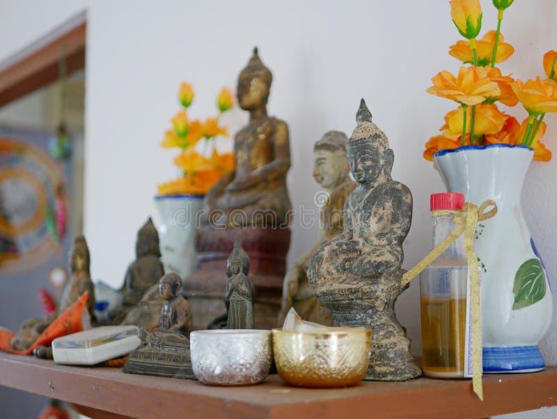 Выборочный фокус различных размеров изображений Будды на полке Hing Phra Будды дома в Таиланде стоковое изображение
