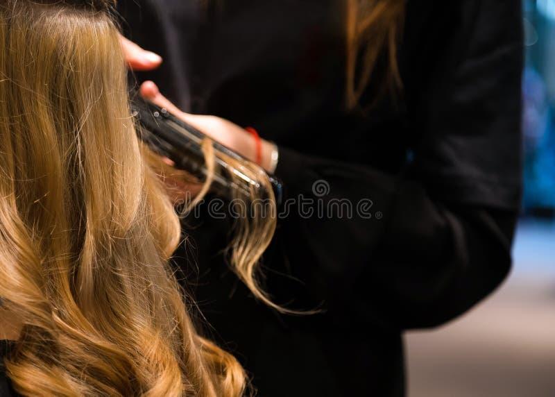 Выправлять волос Закройте вверх милой молодой женщины получает ее волосы выравнил в салоне красоты Парикмахер расчесывает ее стоковое фото rf