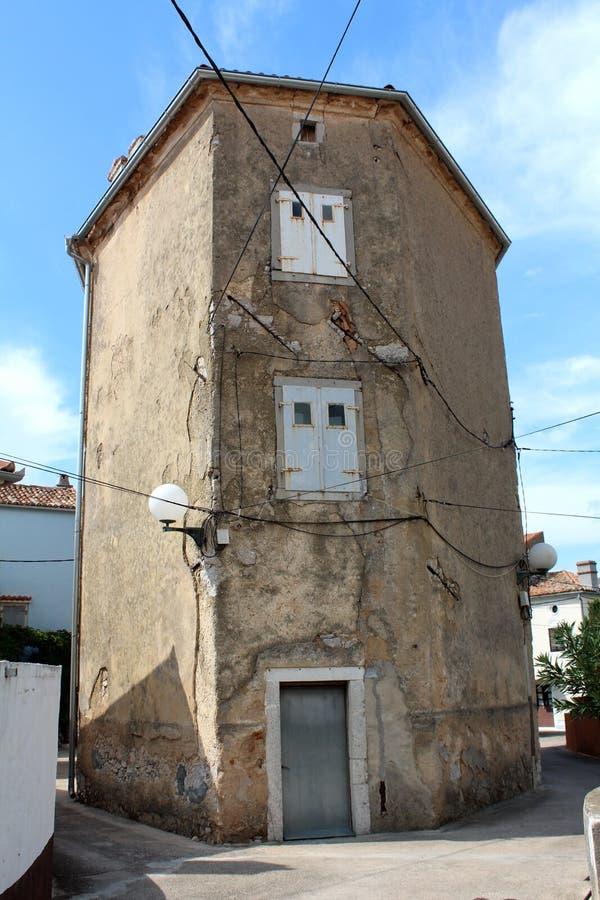 Высокорослое старое здание с разрушанными треснутыми стенами и закрытым окном металла ослепляет на скрещивании пути подключенном  стоковое изображение rf