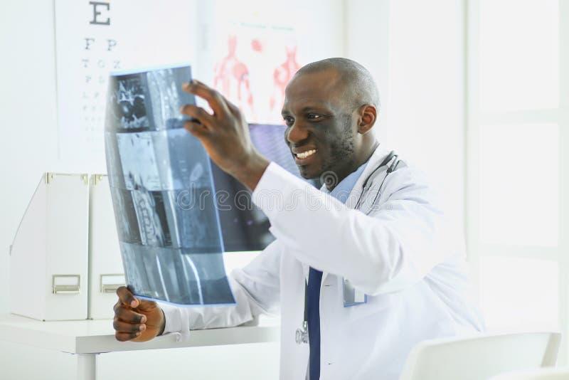 Врач портрета молодой африканский держа терпеливый рентгеновский снимок ` s стоковое изображение
