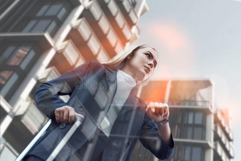 время к пробовать Красивая молодая бизнес-леди в костюме вытягивая багаж и проверяя время пока стоящ против стоковые фотографии rf