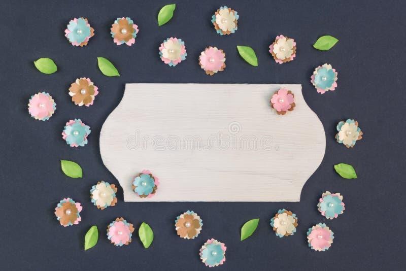 В центре черной предпосылки пустая плита Вокруг хаотично лежать небольшие искусственные бумажные цветки стоковое изображение