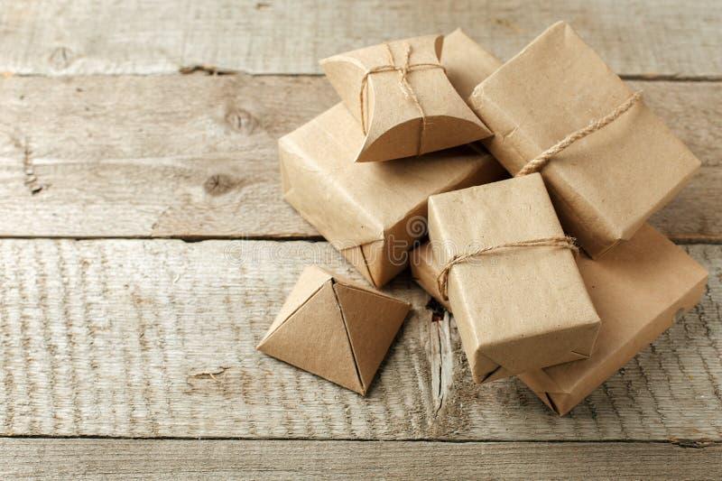 В оболочке подарки на рождество в пакете ремесла бумаги на винтажной деревянной предпосылке, космос экземпляра стильные подарки,  стоковые изображения rf