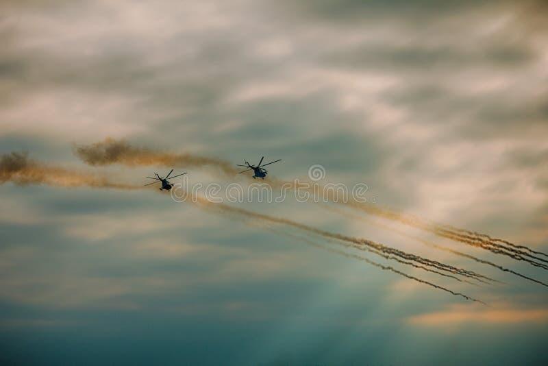 Военный вертолет увольнял ракеты анти--панцыря на заходе солнца стоковые изображения rf