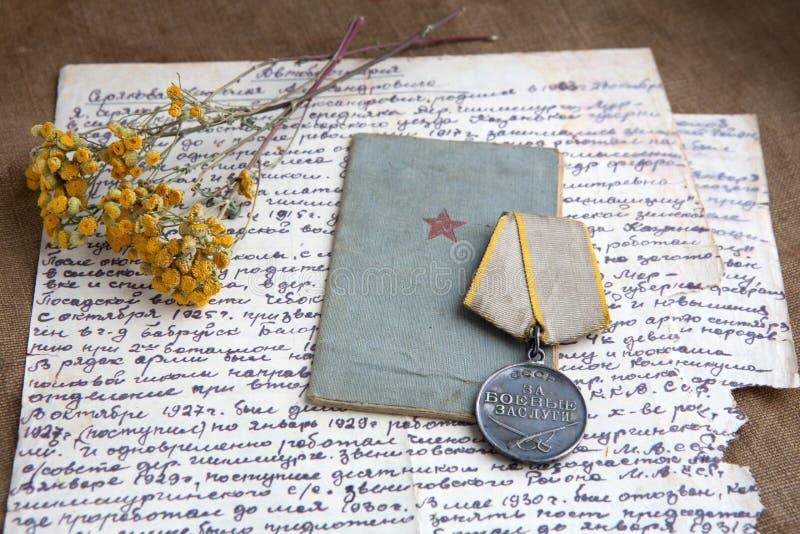 Военное медаль заслуги, старое письмо на холсте Реликвии, конец-вверх Сухие цветки пижмы стоковое изображение rf