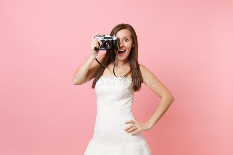 Возбужденная женщина невесты в платье свадьбы фотографирует на ретро винтажной камере фото, выбирая штат, фотограф стоковая фотография