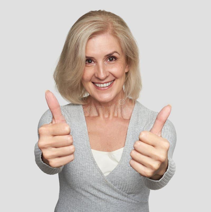 Возбужденная зрелая женщина показывая большие пальцы руки вверх стоковое изображение rf