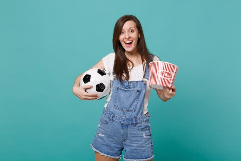 Возбужденная команда поддержки спички футбольного болельщика маленькой девочки наблюдая любимая с футбольным мячом, ведром попкор стоковые изображения rf