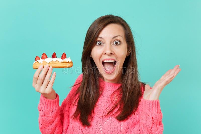Возбужденная маленькая девочка в связанном розовом свитере держа владение рта широкое открытое смотря удивленное в торте eclair р стоковые фото