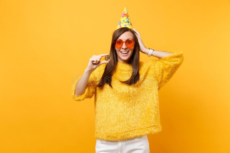 Возбужденная молодая женщина в оранжевых стеклах сердца, шляпа дня рождения кладя руку на главную монетку металла bitcoin владени стоковые фотографии rf