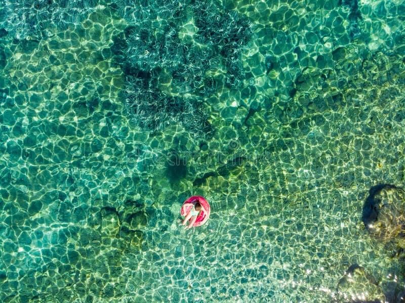 Воздушная верхняя часть вниз с взгляда милой маленькой девочки плавая на кольцо игрушки на пляже Emplisi, живописном каменистом п стоковые фотографии rf