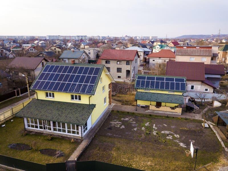 Воздушный взгляд сверху нового современного жилого коттеджа дома с системой панелей голубого сияющего солнечного фото voltaic на  стоковые изображения