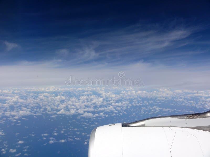 Воздушный над облаками с крылом коммерчески двигателя реактивного самолета с Тихим океаном стоковые фото