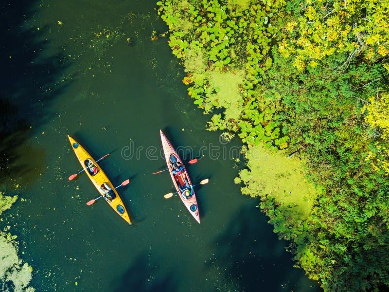 Воздушное фото взгляда глаза птицы трутня счастливой семьи с 2 детьми наслаждаясь ездой каяка на красивом реке Мальчик и стоковая фотография rf