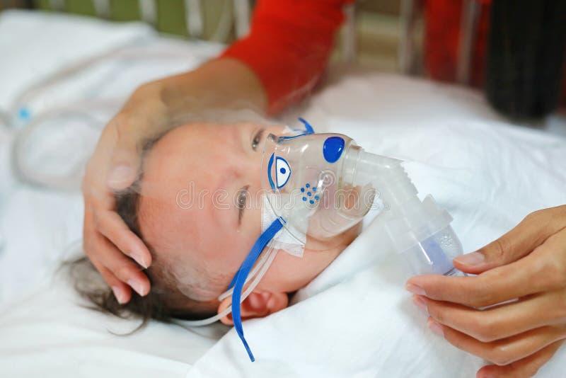 Возраст ребенка вдыхания около 1 лет старый на терпеливой кровати Дыхательный синцитиальный вирус RSV Реанимация на кровати на бо стоковая фотография